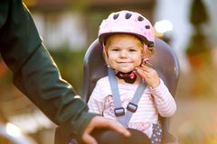 Portrait of little toddler girl with security helmet on the head sitting in bike seat and her father or mother with royalty free stock images