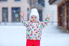 Portrait of little toddler girl walking outdoors in winter. Cute toddler eating sweet lollypop candy. Child having fun royalty free stock image