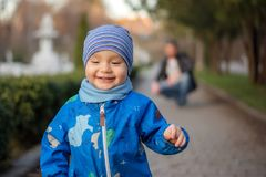 Portrait of a little toddler with a happy tricky face walking along the spring park alley. While His father squatted down in the royalty free stock photo
