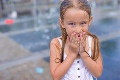 Portrait of little wet happy girl in street Stock Images