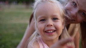 Portrait little young girl with blue eyes looking at camera. Blondy girl smiles gently and looking at camera. Closeup stock footage