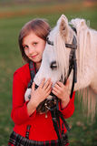Portrait of a little young girl model bnimaet white horse's head and looking at the camera stock photography