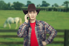 Portrait of lively young cowboy calling on phone Royalty Free Stock Image