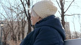 Portrait of a lonely depressed elderly senior woman sitting on a bench in city park in early spring in sunny day -. Apathy, depression and psychology of an aged stock footage