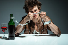 Portrait of a lonely and desperate drunk man trying to break the chains Stock Photos
