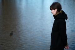 Portrait of a lonely girl by the lake. She stands in black clothes and looks sadly aside, think about the sad thing Royalty Free Stock Photos