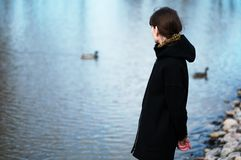 Portrait of a lonely girl by the lake. She stands in black cloth. Es and looks sadly aside, think about the sad thing Stock Photo