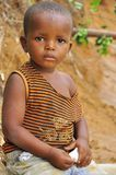 Portrait of lonely sad little african boy. Lonely sad little african boy sitting in the village Royalty Free Stock Photos