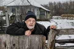 Portrait of lonely Ukrainian old man with tearful face standing at his fence near neglected house in rural Ukrainian village Royalty Free Stock Photos