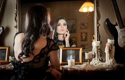 Portrait of long hair brunette girl posing in luxury indoor. Beautiful sexy woman in black lace dress in vintage scenery with candles. Portrait of long hair Royalty Free Stock Images