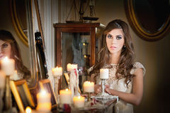 Portrait of long hair brunette girl posing in luxury scenery. Beautiful sexy woman in white lace dress in vintage scenery with candles. Portrait of long hair Royalty Free Stock Photos
