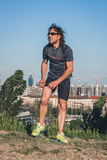 Portrait of a long haired athlete posing in a city park Royalty Free Stock Photography