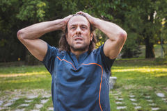 Portrait of a long haired athlete stretching in a city park Stock Photo