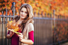 Portrait of long-haired beautiful girl with maple leaves in knit Royalty Free Stock Photo
