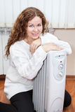 Portrait of long-haired curly woman near oil heater Royalty Free Stock Images