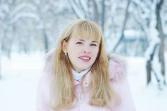 Portrait of a long-haired cute blonde young woman outdoors in winter. Portrait of a long-haired cute blonde young woman outdoors in a winter park Stock Photo