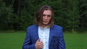 Portrait of a long-haired handsome young man in a business suit in a park. stock video