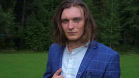 Portrait of a long-haired handsome young man in a business suit in a park. stock footage