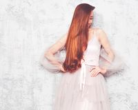 Portrait of a long-haired red-haired girl posing against a gray stone wall in a beautiful airy pink dress Stock Photos