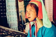 Portrait of long neck woman in traditional costume. Karen long neck tribe northern Thailand. Portrait of Long Neck Woman weave cloth in front her house in tribal royalty free stock photography