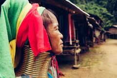 Portrait of long neck woman in traditional costume. Karen long neck tribe northern Thailand. Portrait of Long Neck Woman weave cloth in front her house in tribal royalty free stock photo
