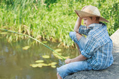 Portrait of looking down on pond water angling boy Royalty Free Stock Images