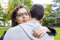 Portrait of love couple embracing outdoor in park looking happy Royalty Free Stock Image