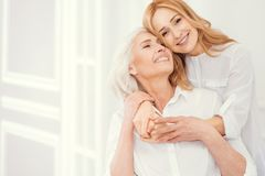 Portrait of loveful mature daughter embracing her elderly mom. Forever thankful. Sweet moment of expressing love between retired mother and her loving daughter Stock Photo