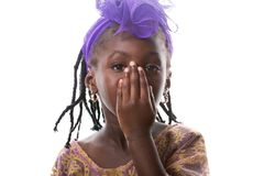 Portrait of a lovely African little girl cover face own arm,isolated. Portrait of a lovely African little girl cover face own arm in purple costume on white stock photos
