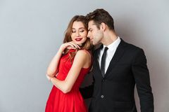 Portrait of a lovely attractive couple dressed in formal wear. Posing while standing and hugging over gray wall background Stock Image