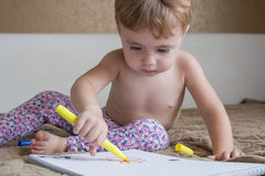 Portrait of lovely baby drawing with colorful pencils stock images