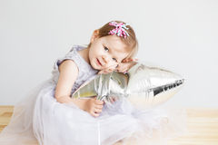 Portrait of a lovely baby girl playing with silver star-shaped b Stock Image