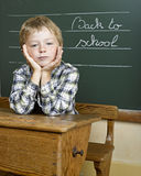 Portrait of lovely boy at school. Looking at camera in front of a blackboard Royalty Free Stock Photos