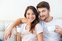 Portrait of lovely couple on the couch drinking coffee Stock Photography