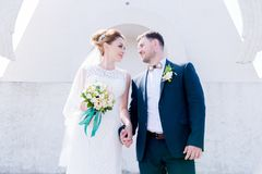 Portrait of a lovely couple honeymooned on a wedding day with a bouquet in hand against the background of an Orthodox. Christian monument with angels. The Royalty Free Stock Photo