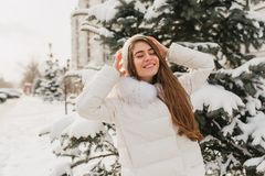 Portrait lovely cute girl chilling on sunshine in frozen morning. Young joyful woman enjoying winter time on fir trees royalty free stock image