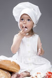 Portrait of Lovely Female Kid Posing as Cook. Tasting Food with Fingers Stock Photo