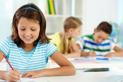Girl drawing. Portrait of lovely girl drawing at workplace with schoolmates on background royalty free stock image