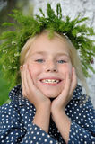 Portrait  lovely girl in a grass head wreath. Portrait of a cute lovely girl in a grass head wreath Royalty Free Stock Image
