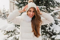Portrait lovely girl with long light-brown hair showing true happy emotions in winter day on fir tree background. Portrait of  lovely girl with long light-brown stock photo