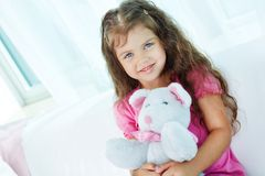 Girl with teddybear. Portrait of lovely girl with teddybear sitting on sofa at home Royalty Free Stock Images