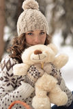 Portrait of lovely girl with cute,nice toy.Cute,beautiful,nice girl hug a fluffy,white,beige teddy bear.Girl and bear in winter Royalty Free Stock Photo