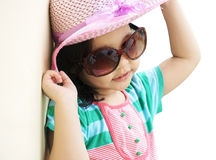 Portrait of lovely girl wearing pink dress, hat and glasses isolated on white background Stock Image