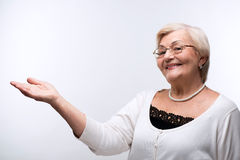 Portrait of lovely grandmother showing copy space. Grandmother advertising your product. Closeup of a beautiful senior woman holding copy space on her hand and Royalty Free Stock Photo