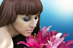 Portrait of lovely lady looking at flowers and smelling them Royalty Free Stock Photography