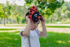 Portrait lovely little boy in the park. Attractive handsome young boy is putting the mask for playing in garden in evening. Lovely stock images