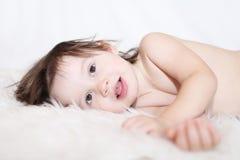 Portrait of lovely little child lying on white fur rug Stock Photos