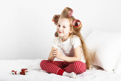 Portrait of a lovely little girl with big curlers on her head ea Stock Photos