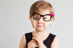 Portrait of a lovely little girl with funny paper glasses agains Stock Images
