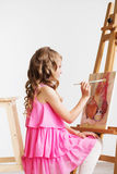 Portrait of a lovely little girl painting a picture in a studio Royalty Free Stock Photography